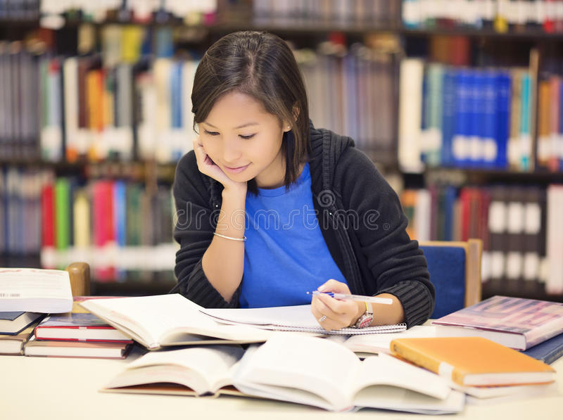 Student sitting and reading book in library stock photography