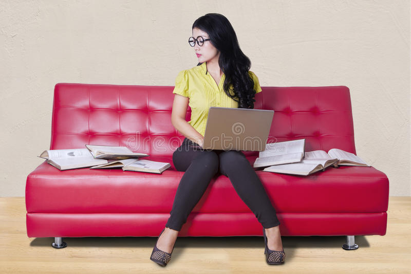 Student sitting on sofa while doing homework. Female high school student with long hair, sitting on the sofa while doing homework with laptop and books royalty free stock images