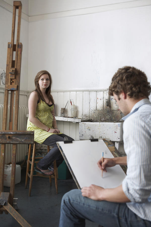 Student Sketching Model In Art Class. Male student sketching female model in art class royalty free stock images