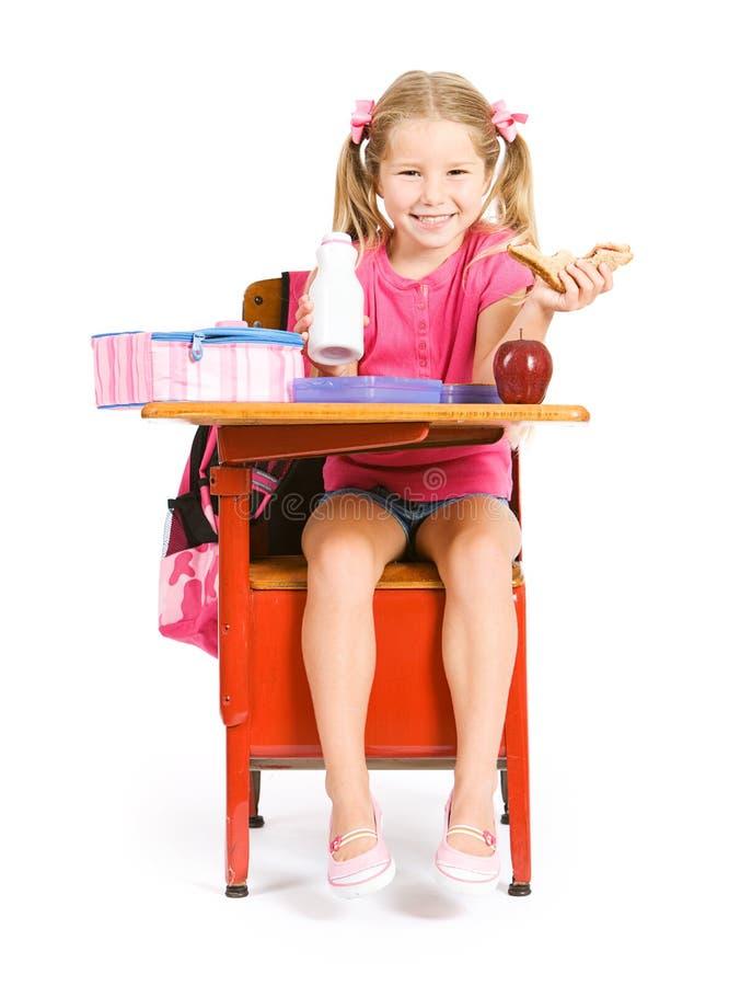 Student: Skratta flickan som har lunch p? skolaskrivbordet arkivfoto