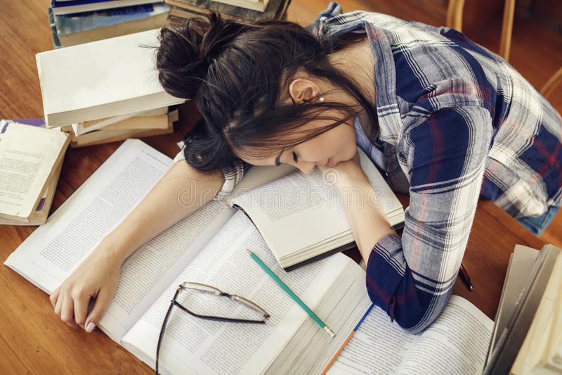 Student sleeping at the paper books royalty free stock image