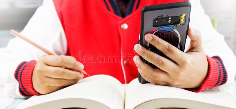 Student som använder den smarta telefonen i grupp royaltyfri foto
