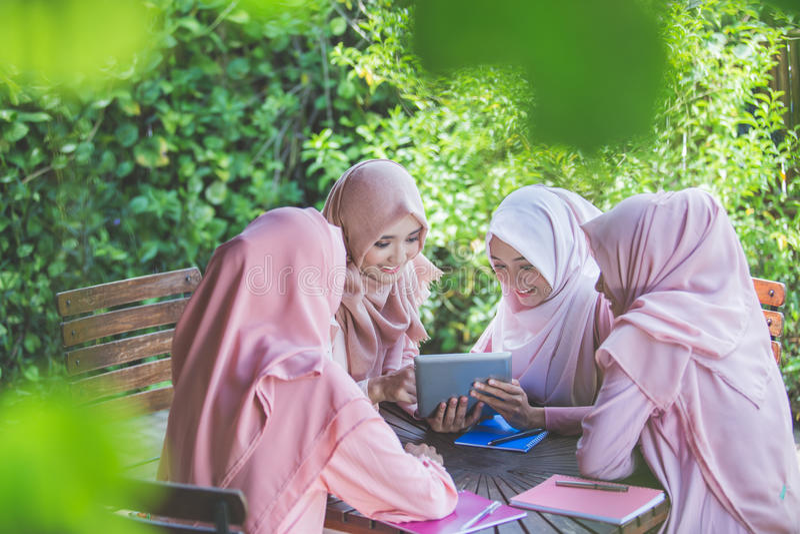 Student som använder minnestavlaPC i kafé med vänner arkivbilder