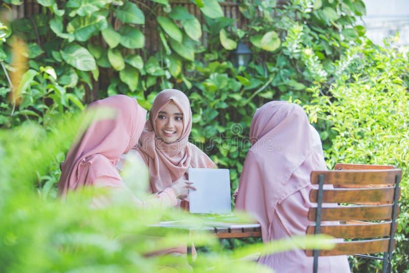 Student som använder minnestavlaPC i kafé med vänner royaltyfri bild