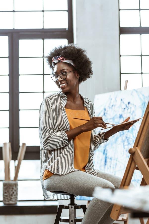Student som bär grå damasker och skjortamålning i seminarium fotografering för bildbyråer