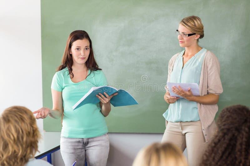 Student som förklarar anmärkningar förutom lärare i grupp royaltyfri bild