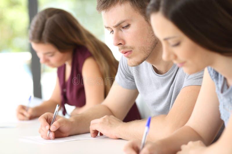 Student som kopierar en examen av en klasskompis royaltyfria bilder