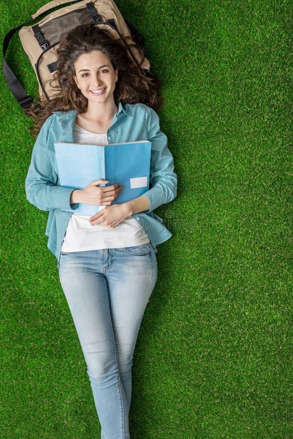 Student som kopplar av på gräset fotografering för bildbyråer