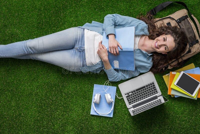 Student som kopplar av på gräset royaltyfria bilder