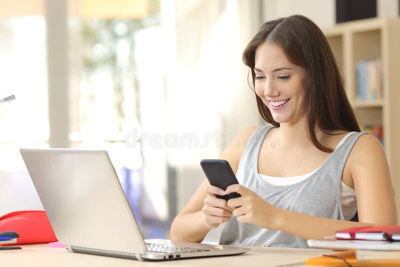 Student som lär med bärbara datorn och mobiltelefonen royaltyfria bilder