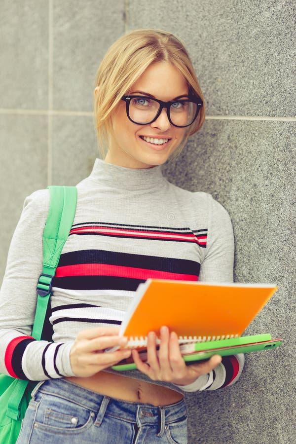 Student som ler den hållande anteckningsboken på den gråa väggen royaltyfri fotografi
