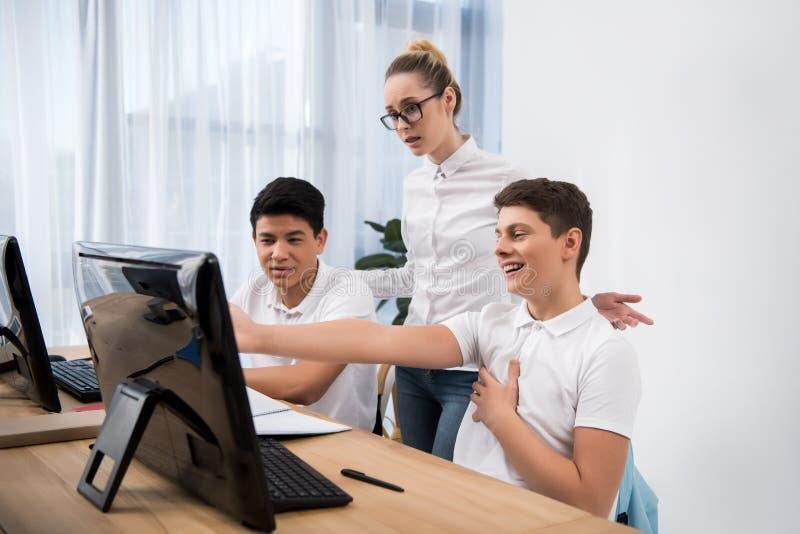 student som pekar på skärmen till hans klasskompisar royaltyfri foto