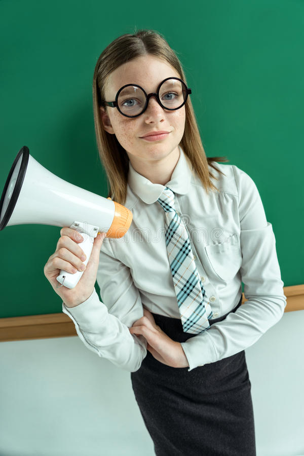Student standing near blackboard with a megaphone. Photo of teen school girl wearing glasses, creative concept with Back to school theme stock photography