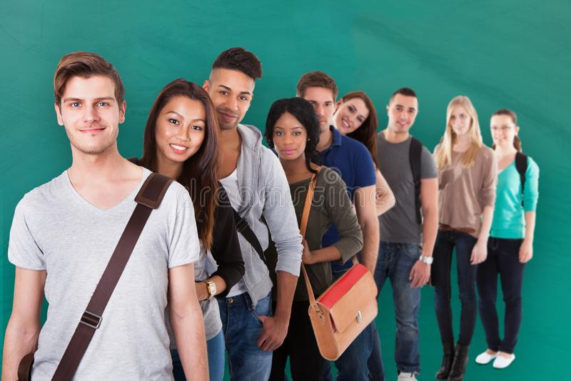 Student Standing In Row mot grön bakgrund royaltyfria foton