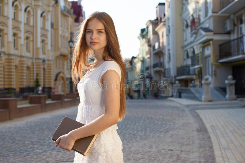 Student on street. Happy student with book on street royalty free stock photography