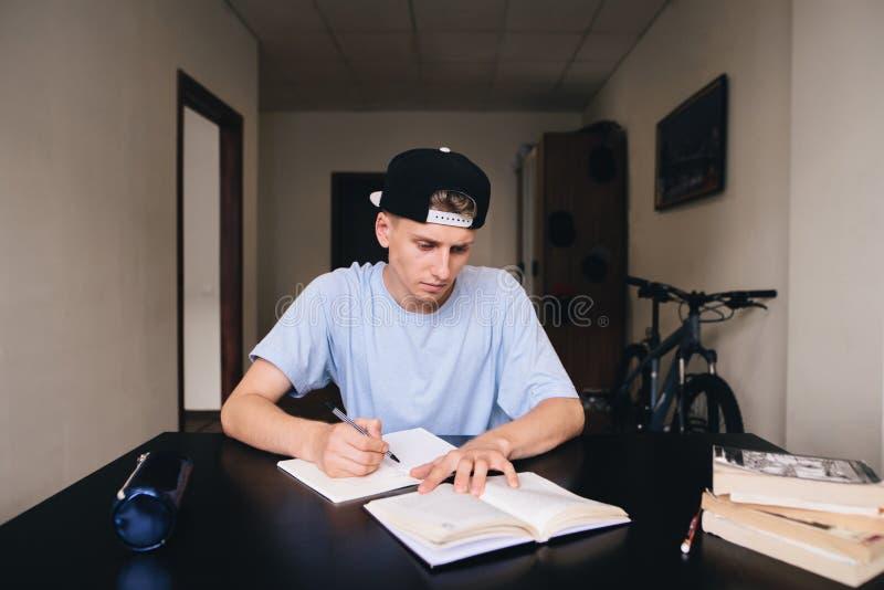 Student studiert zu Hause Er notiert sorgfältig die Aufgaben und die Antworten in seinem Notizbuch heimarbeit lizenzfreie stockfotografie