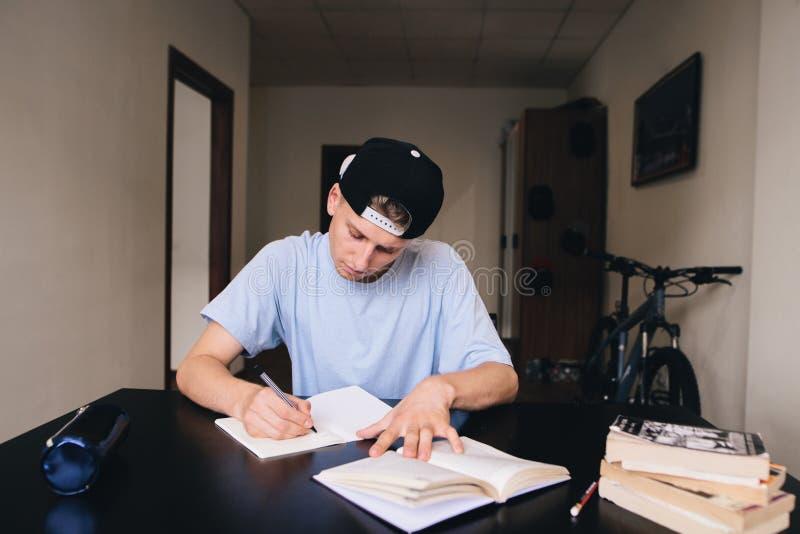 Student studiert zu Hause heimarbeit Ein jugendlich mit einem genauen Blick schreibt den Text zu seinem Notizbuch stockfotos
