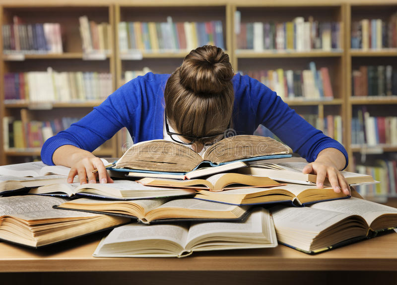 Student Studying, die op Boeken, Vermoeid die Meisje slapen in Bibliotheek wordt gelezen stock afbeelding