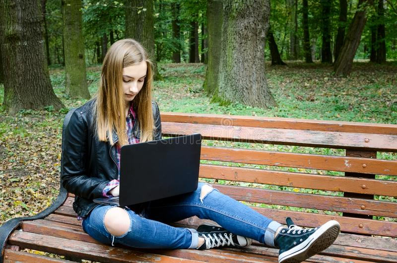 Student studying outdoors. Young woman keyboarding on laptop computer while sitting on the bench in park. Blonde female teen working on net-book after her stock photo