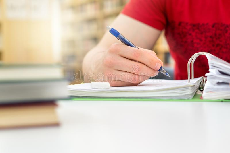 Student studying and writing notes in public or school library. Young athletic man and student studying and writing notes in public or school library in college royalty free stock photo