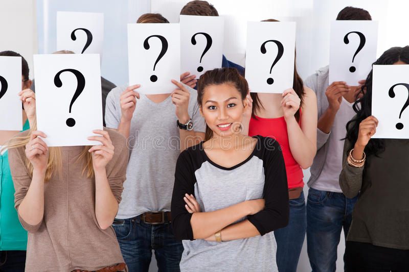 Student surrounded by classmates holding question mark signs royalty free stock image