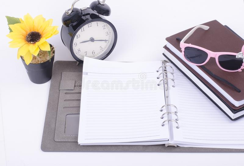 On student table item contain vintage clock, artificial flower plant and stacking diaries. Over white background stock photography