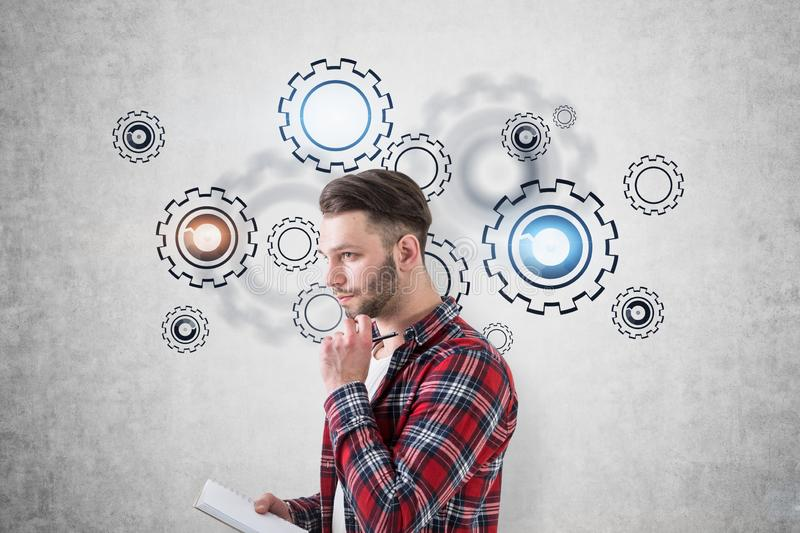 Student taking notes, gears and cogs. Pensive young bearded student in casual clothes taking notes standing near concrete wall with gears drawn on it. Concept of royalty free stock photography