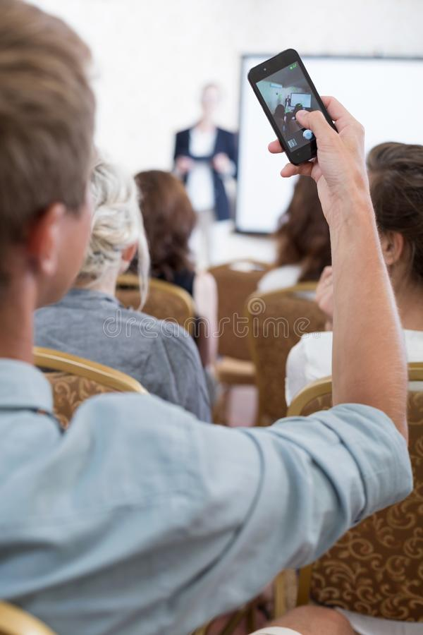 Student taking photo during conference stock photography