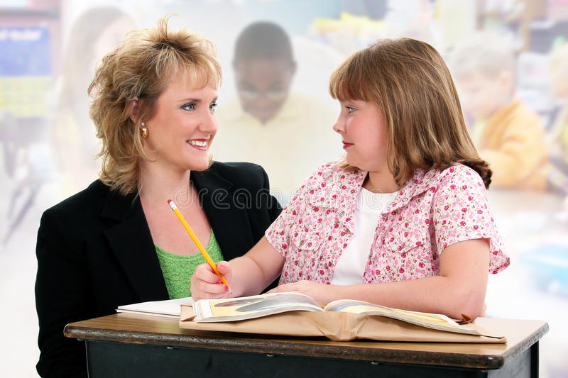 Student and Teacher at Desk in Classroom. royalty free stock photography