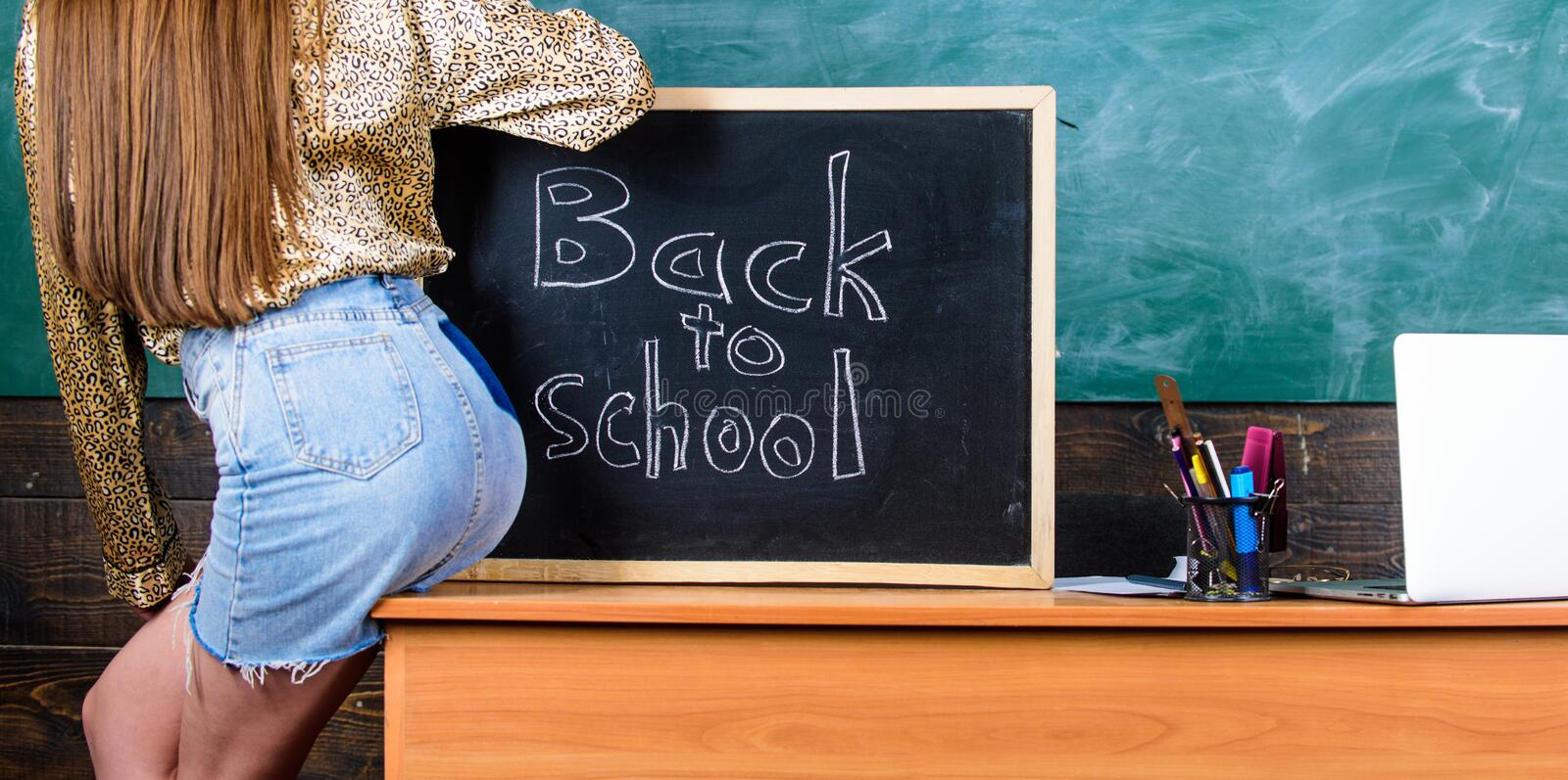 Student teacher mini skirt buttocks sit table blackboard inscription back to school. Girl denim skirt breaking stock photos