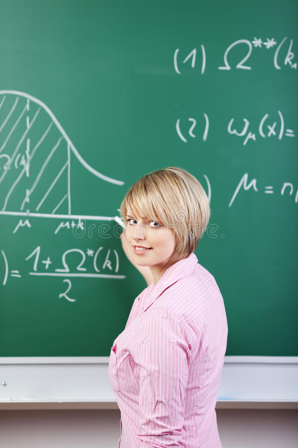 Student or teacher writing on the blackboard. Attractive young student or teacher writing on the blackboard in a classroom at college or university drawing stock image