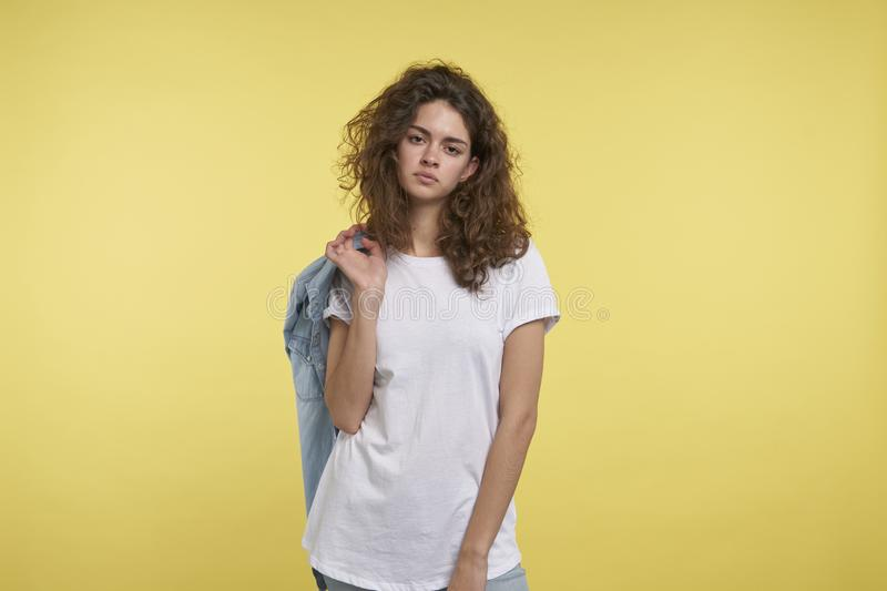 Pretty brunette teenager female with curly hair stands isolated over yellow background royalty free stock photo