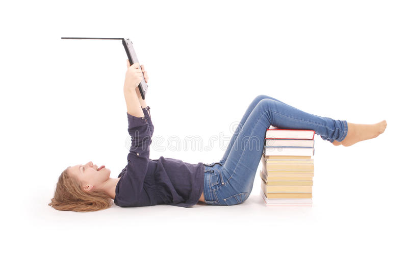 Student teenage girl lying sideways on the floor with laptop. Isolated on white royalty free stock photography