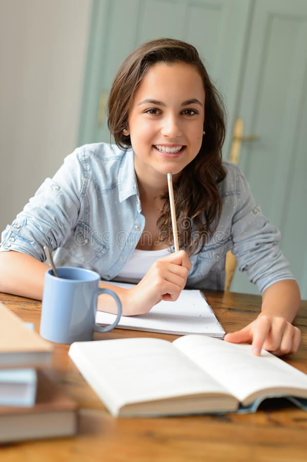 Student teenage girl studying at home smiling royalty free stock photography