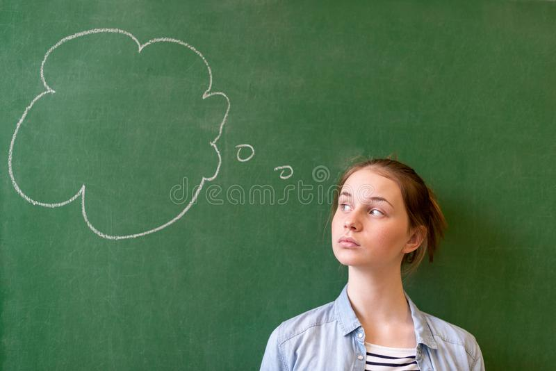 Student thinking blackboard concept. Pensive girl looking at thought bubble on chalkboard background. Caucasian student. stock photos