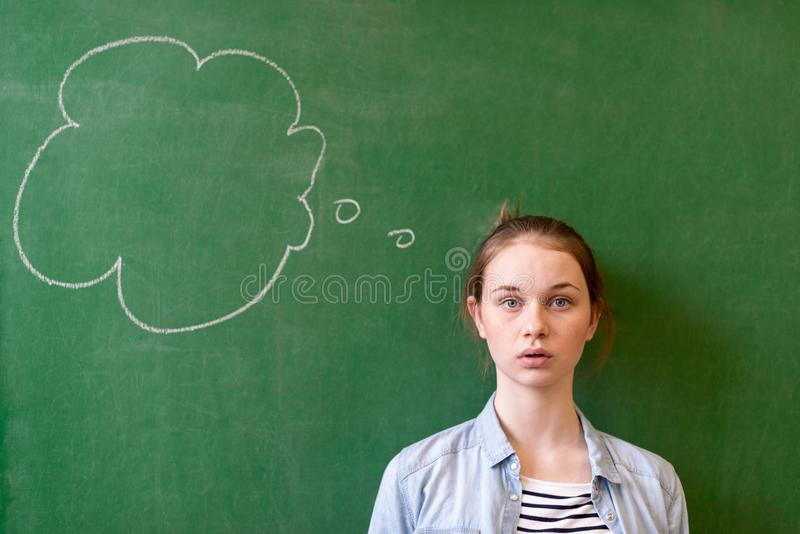 Student thinking blackboard concept. Pensive girl looking at thought bubble on chalkboard background. Caucasian student. royalty free stock photography