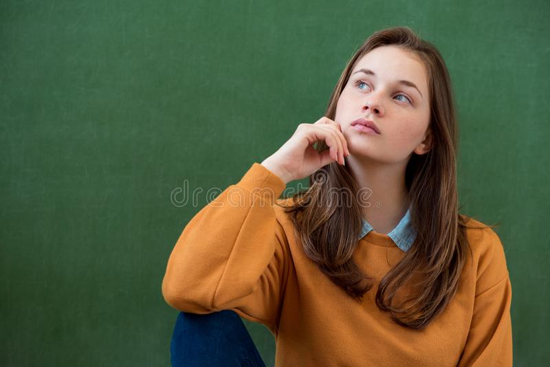 Student thinking and leaning against green chalkboard background. Pensive girl looking up. Caucasian female student portrait. royalty free stock image