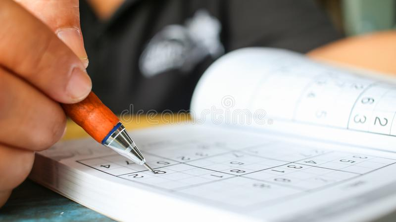 Student is trying to solve sudoku with color pencil as hobby a royalty free stock images
