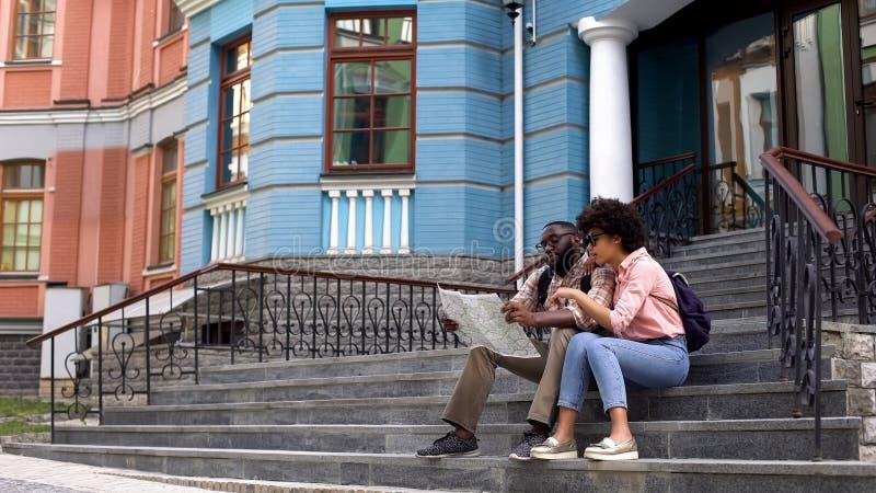 Student uniwersytetu patrzeje mapę, siedzi na budynków schodkach, zwiedzająca wycieczka zdjęcia stock