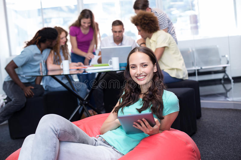 Student using digital tablet with friends in background stock photo