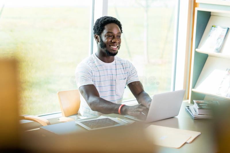 Student Using Laptop While Studying In Library royalty free stock photos