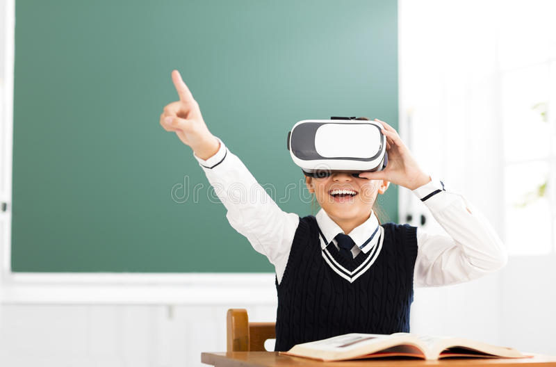 Student with virtual reality headset sitting in classroom stock image