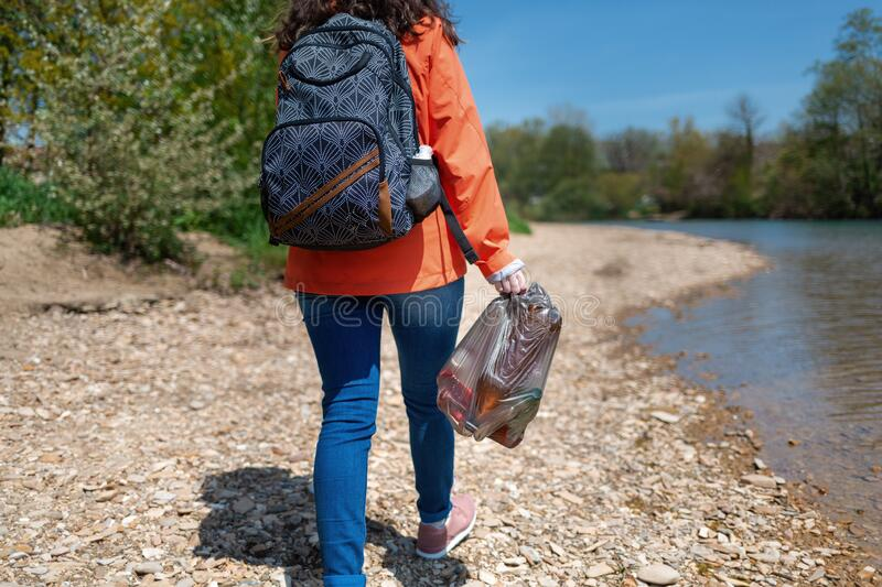 Student volunteer walks along the river Bank with a garbage bag and removes garbage. The concept of conscious behavior and love of stock photography