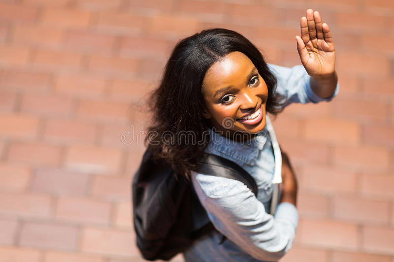 Student waving goodbye. Overhead view of african american student waving goodbye royalty free stock photography