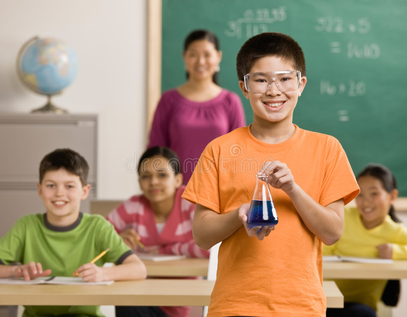 Student wearing goggles holds beaker of liquid royalty free stock photography