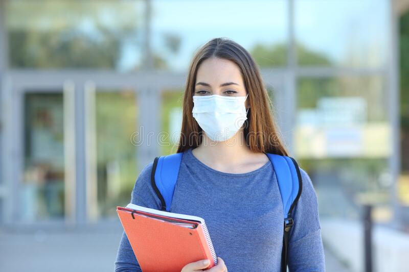 Student wearing a mask walking in a campus royalty free stock photo