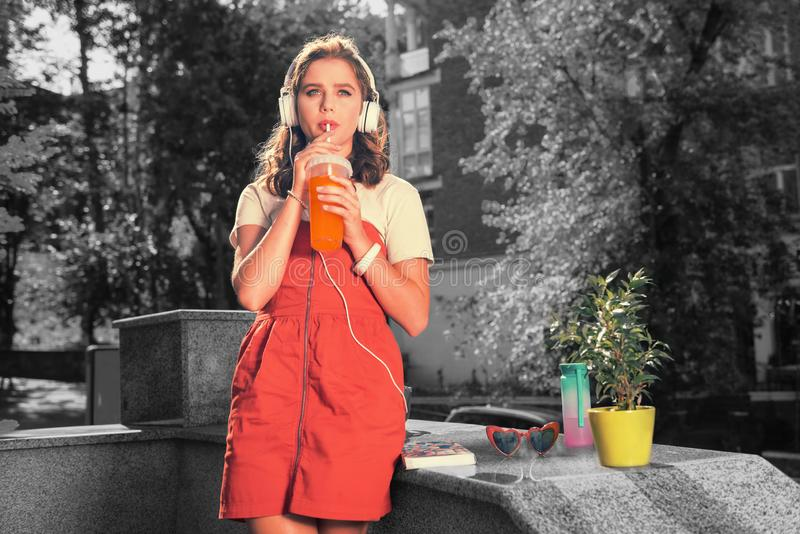 Student wearing red summer dress feeling amazing drinking summer refreshing juice royalty free stock photos