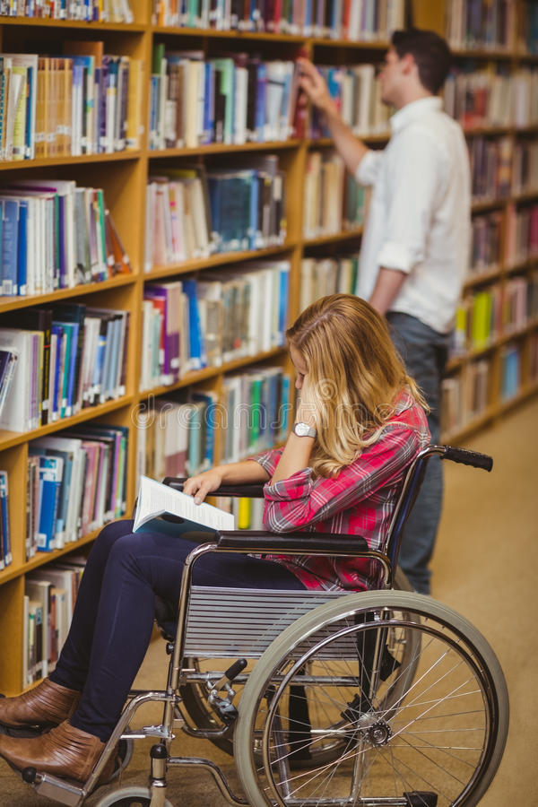 Student in wheelchair talking with classmate. In library royalty free stock photo