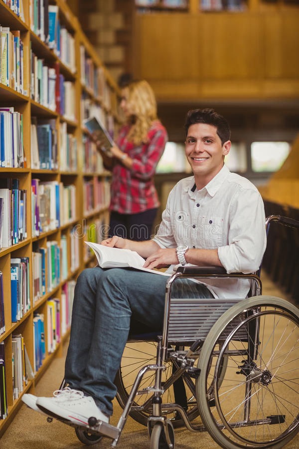 Student in wheelchair talking with classmate. In library royalty free stock image