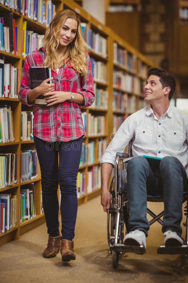 Student in wheelchair talking with classmate. In library royalty free stock photography